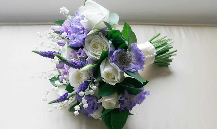 Pretty hand tied bouquet of ivory roses, blue scabious, blue veronica, lavender lisianthus. lily of the valley and ruscus foliage.
