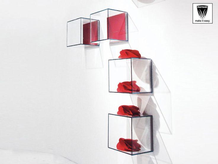 Kube Espositore con struttura a cubo in alluminio, con pareti in plexiglass trasparente. Leggero e facile da appendere, con fondo a parete colorato.