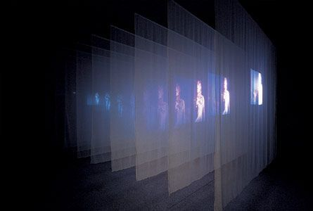 The Veiling, 1995. Video/sound installation, including two channels of color video projections from opposite sides of dark Gallery through n...