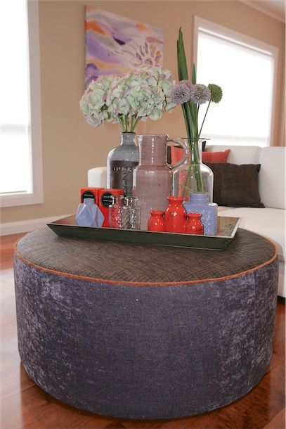 Custom made round ottoman styled with decorative homewares and florals.