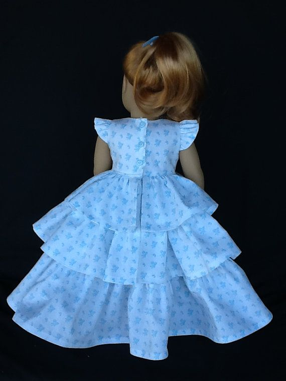 So pretty on Maryellen and other 18 inch dolls. This style is typical of the 1950s  I used a cotton print with a white background and tiny blue bouquets of flowers.  The dress features a lined bodice with ruffled sleeves and closes in the back with four tiny white buttons and buttonholes .  The skirt has three really full gathered ruffles. I attached a blue ribbon at the waist for added interest.  All seams have been surged for a neat finish. Made by me in my smoke free home.