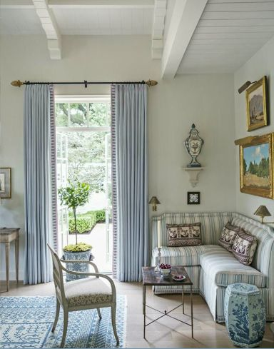 A blue and white Samarkand pattern custom oriental rug complements lavender-tinged gray walls and red and gold accents add warmth to Cathy Kincaid's living room design.