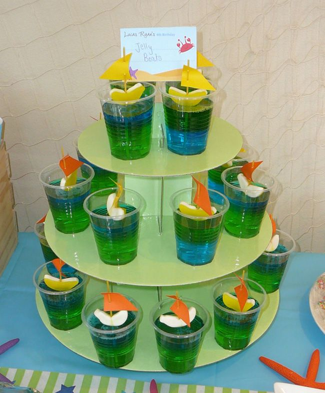 """These jello boat desserts are made of blue and green jello """"water"""" with gummy fruit slice """"boats"""" on top. The sails are made from slips of paper and pieces of dry spaghetti. Adorable!"""