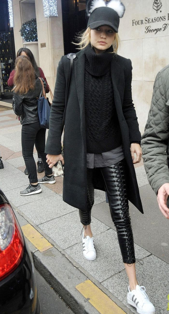 She paired her racy lace-up faux leather jeans with a cable-knit bulky black turtleneck sweater layered over an oversized grey t-shirt and a Charlotte Simon pom baseball cap
