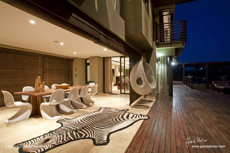 Lardge wooden outdoor dining, feature plastic outdoor chairs, zebra carpet, hanging chair, downlights, wooden blinds