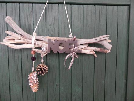 6 branches de bois flottées reliées entre elles accueillent le mot NOEL avec ses 2 clochettes et ruban vichy marron  deux pommes de pins sont suspendues  Largueur totale 42 c - 19200110
