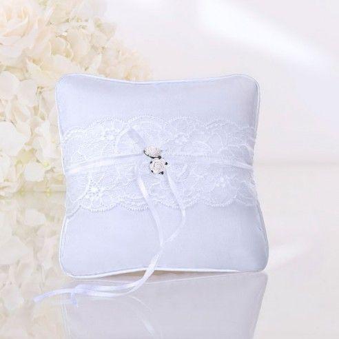Witte kant, wit lint en witte roosjes staan centraal in de trouwaccessoires van de White Vintage collectie. Het ringkussentje van deze collectie is voorzien van extra lange lintjes om de ringen te kunnen bevestigen.