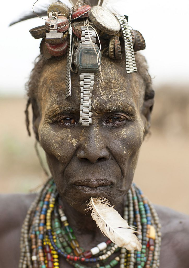 An elderly woman from the Dassanetch tribe customises her bottle cap wig with watches from China. Omo Delta, Ethiopia (picture by Eric Lafforgue)