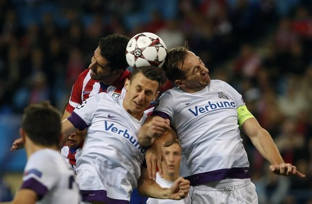 Atletico Madrid's Garcia fights to head ball with Austria Vienna's Mader and Ortlechner during their Champions League Group G soccer match a...