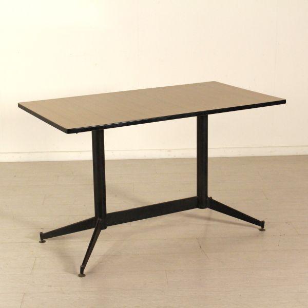 Tavolo anni 60 con base in metallo; piano in legno ricoperto in formica. Buone condizioni; presenta piccoli segni di usura.