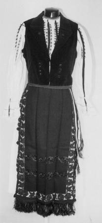Romanian Women's costume from county of Sibiu Blouse (ie) made of white cotton, decorated with black embroidery called Punctul 'Ciocănele'  which gives the appearance of vertical bands of  black braid on the sleeves and front of the blouse.  Black velvet waistcoat  (ilic)