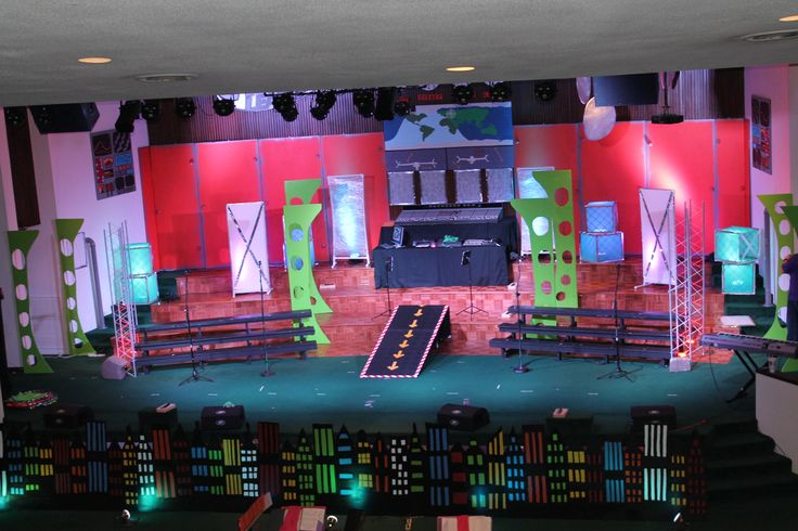 """Our full set for the Agape League.  Most things are made out of pink insulation board.  The city skyline is at the bottom.  The entire stage was the fortress.  We added light boxes made from aircondition filters and light panels made from pvc pipe .  Two are covered in white cloth and tape and two are covered in saran wrap.  The """"radar"""" panels at the top right are hula hoops wrapped in saran wrap"""