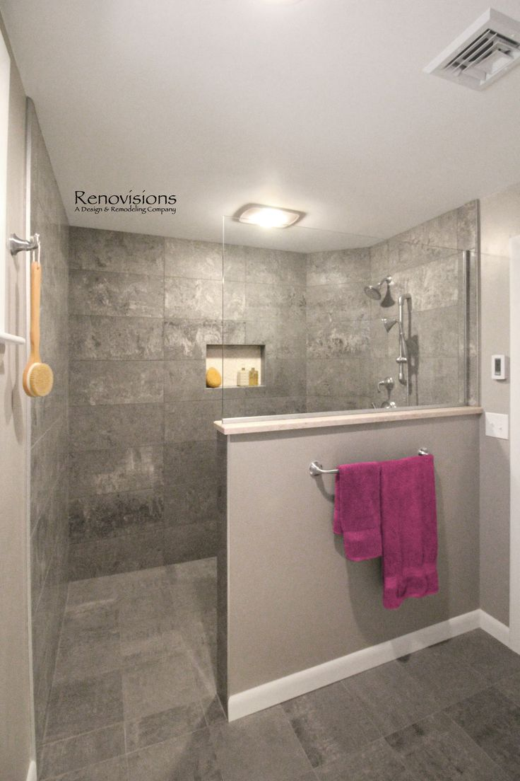 A completed master bathroom remodel by Renovisions. Walk-in shower, open shower, contemporary design, half wall, porcelain tile, large format tile, shower cubby, lineal drain, curbless shower, hand-held shower, toilet cubby, quartz countertop, pocket door.