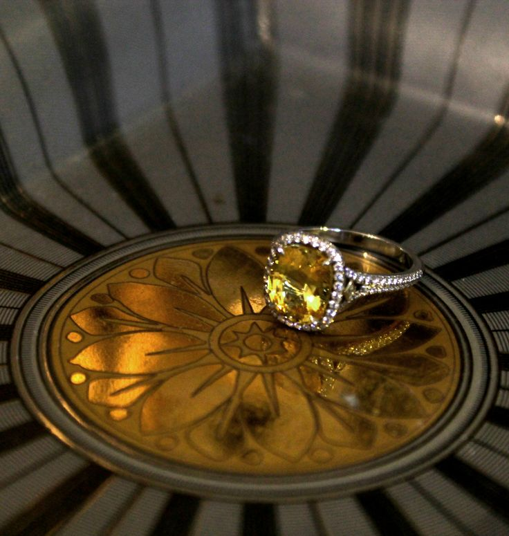 Tiffany & Co. yellow sapphire engagement ring set in platinum with white diamonds. Proposal idea? Resting on a vintage antique plate with a gold flower mandala pattern, reflecting the bright yellow sapphire. http://www.thejewelleryeditor.com/bridal/article/sapphire-engagement-rings-number-one-coloured-gem/ #wedding