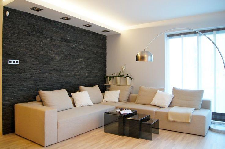 Sofa, lampa, kamień na ścianie