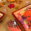 Rich-hued plates with seasonal patterns sit prettily atop chargers, paired with the utensils in napkin pockets on the side
