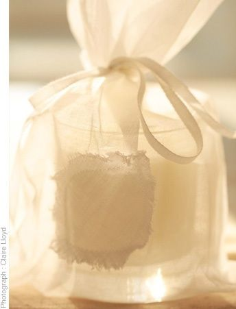 Hand pored scented candles in glass packaged in Organdie. Scents are either Rose geranium or Jasmine