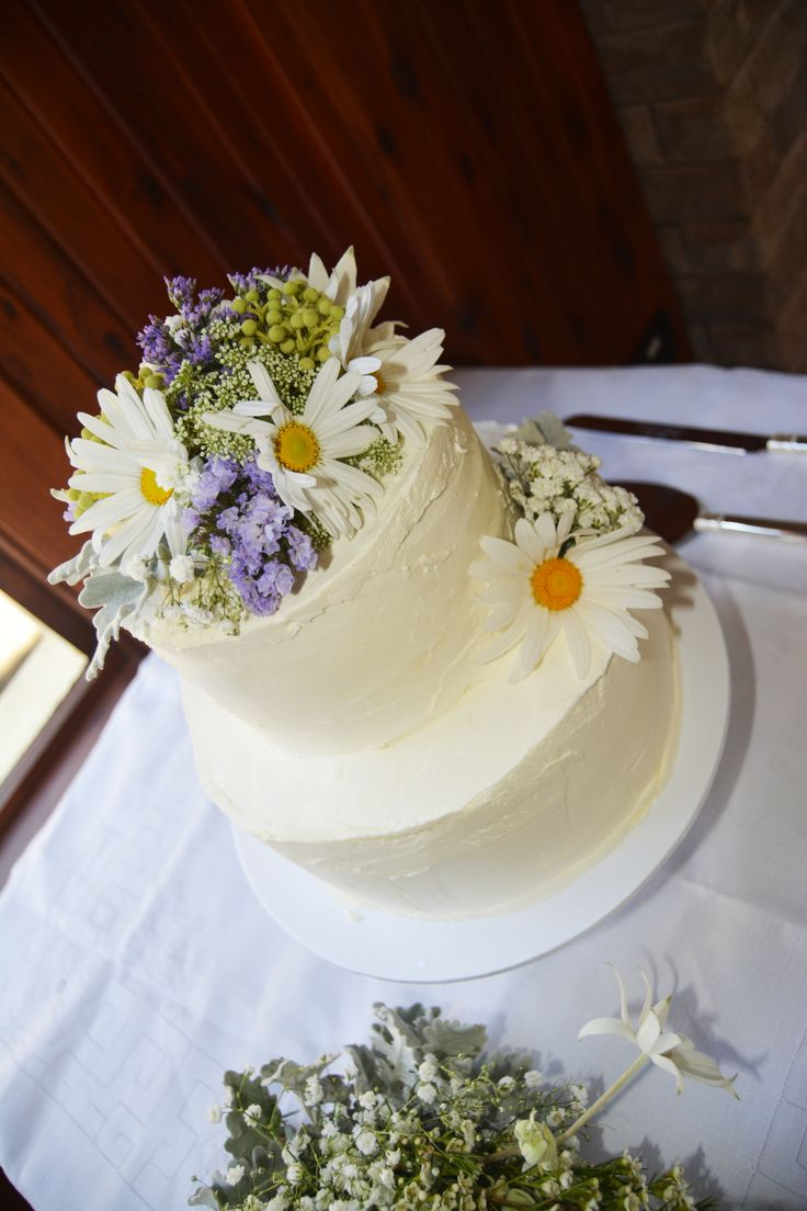 a 2 tiered rustic texturized butter cream cake with fresh flowers.
