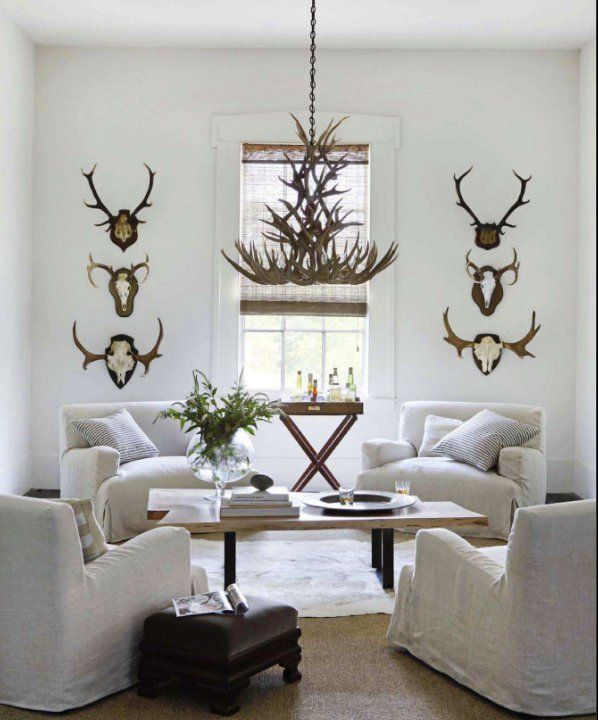 Farmhouse Chic White Living Room Design Featuring Antler Wall Decor And Chandelier