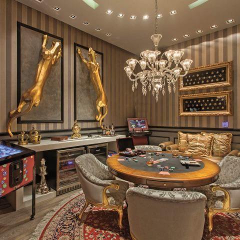 Sala de Jogos - Val Munhoz e Maxwell Geraldi - As suntuosas salas dos cassinos foram a inspiração do projeto, que investe nos detalhes em dourado. O luxo também está na composição entre os tecidos, a tapeçaria e o papel de parede, bem como no lustre em cristal.