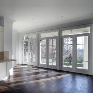 Three white French doors with transoms and dark hardwood floors.