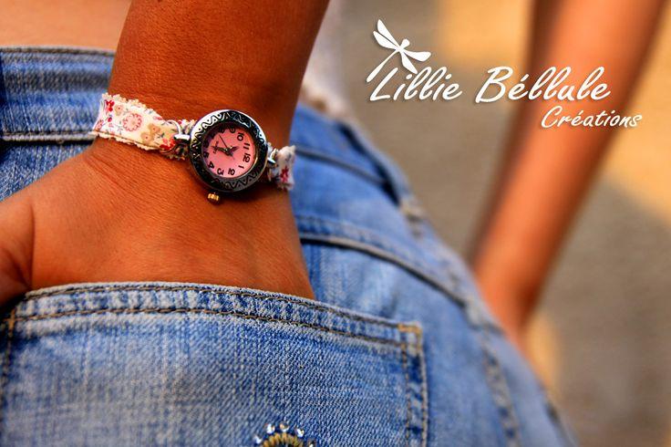 Montre argentée montée sur un bracelet en tissu fleuri rose et blanc bordé d'une fine dentelle. Fermoir mousqueton et chainette argentée.