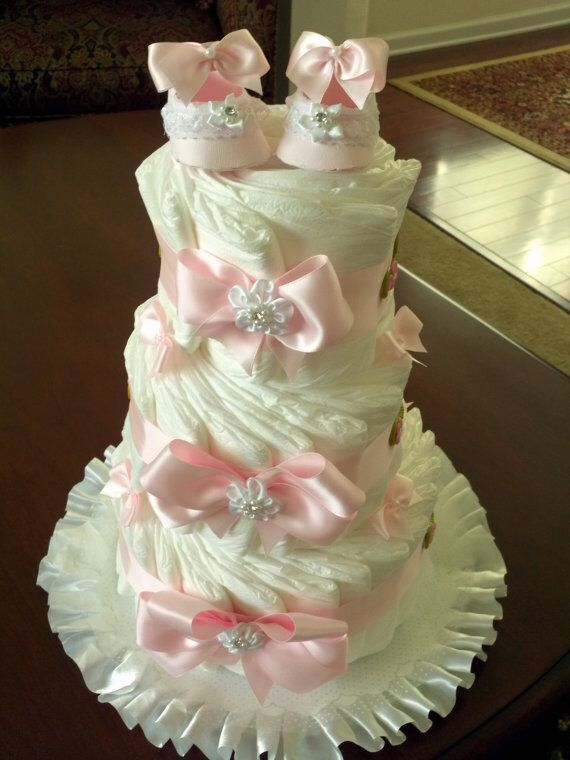Three Tier Pink and White Diaper Cake with Decorative Booties by TheCarriageShoppe on Etsy https://www.etsy.com/listing/157020372/three-tier-pink-and-white-diaper-cake
