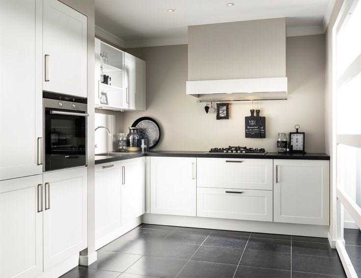 Een moderne keuken met landelijke accenten zoals de kaderdeurtjes en de schouw. De strakke grepen creëren een moderne look.