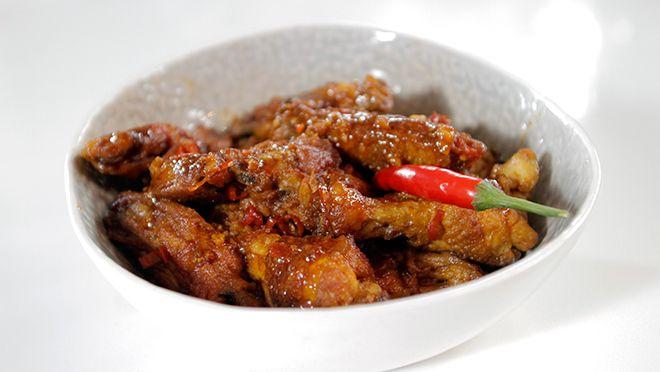 nijd de rode pepers fijn.  Leg de kippenvleugels in een schaal zodra ze klaar zijn. Giet de helft van de olie uit de pan. Voeg de knoflook, peper,...