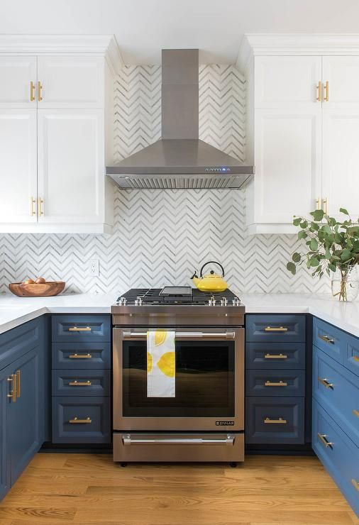U-shaped blue kitchen cabinets accented with brass pulls flank a stainless steel hood fixed against white and gray chevron wall tiles beneath a stainless steel hood flanked by stacked white cabinets adorned with brass hardware.