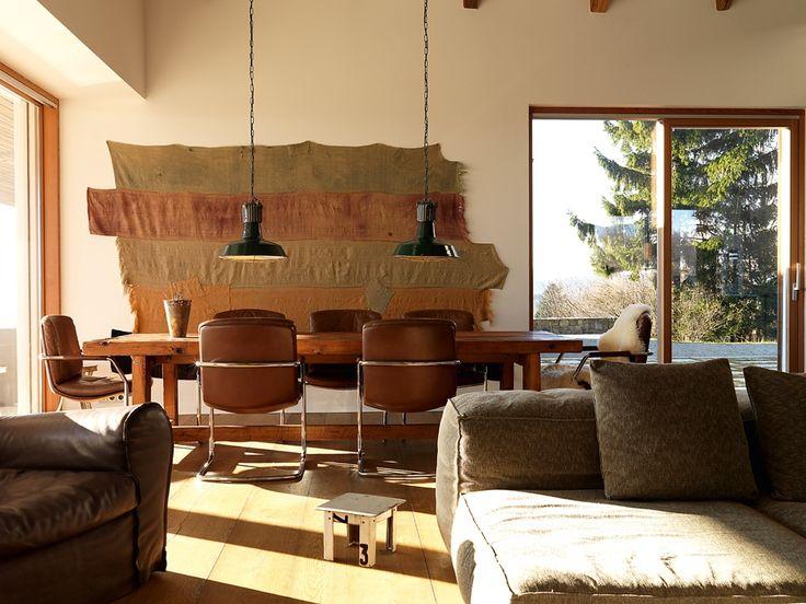 AUSTRIA Nella campagna vicino a Wiener Neudorf, in Bassa Austria, lo studio Malek Herbst Architekten ha realizzato un intervento di recupero volto a ripristinare l'architettura originale della cascina, rendendola eco-sostenibile.  All'interno predominano i toni caldi del legno dei mobili, fatti su misura dai progettisti, e del parquet. Sul tavolo in legno massiccio due lampade industriali a sospensione. In primo piano sofà Living Divani Foto Gerhard Liebminger