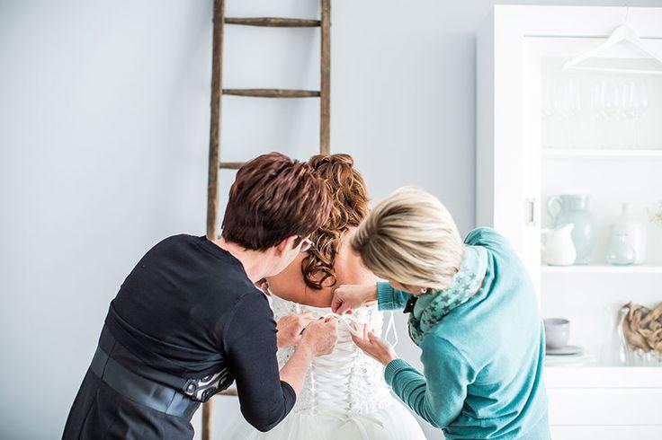 Bruid wordt in jurk geholpen door moeder