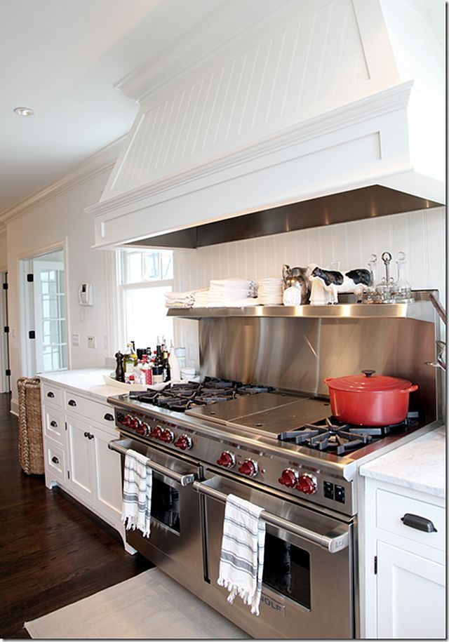 double oven Wolf range, stainless steal backdrop and white cabinets with matte black drawer pulls