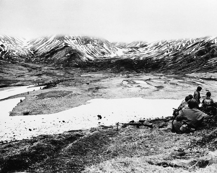 Description of  July 6,1943: Across this valley on Attu up above the fog line that obscures the tops of the mountains lie the passes that lead to Holtz Bay and Chichagof Bay. In the Valley at right center leading back into the mountains are strong Japanese positions shown. Attu Island was the site of the only World War II land battle on United States soil. (AP Photo)