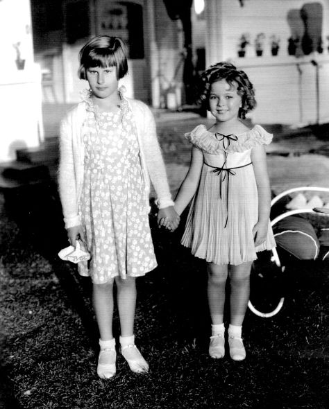 Shirley Temple with a visitor on the set of Curly Top, 1935.