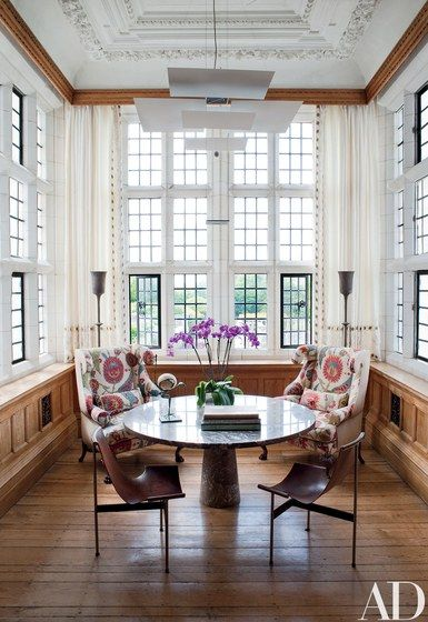 The custom-made Georgian-style wing chairs in the library alcove are upholstered in a hand-embroidered fabric from Robert Kime; the pendant lamp is by Maurer, and the TG-10 sling chairs and marble Angelo Mangiarotti table are vintage | archdigest.com
