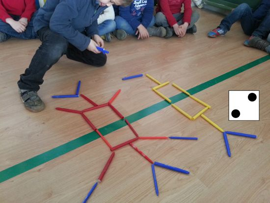 replica- Team 1 roll dice, take that many pieces of one colour and make pattern. Team2 replicates pattern on their side of the symmetry line. Team 2Player rolls dice and makes pattern on their side for team1 to copy. Can make new structure or… add onto existing by using a different colour