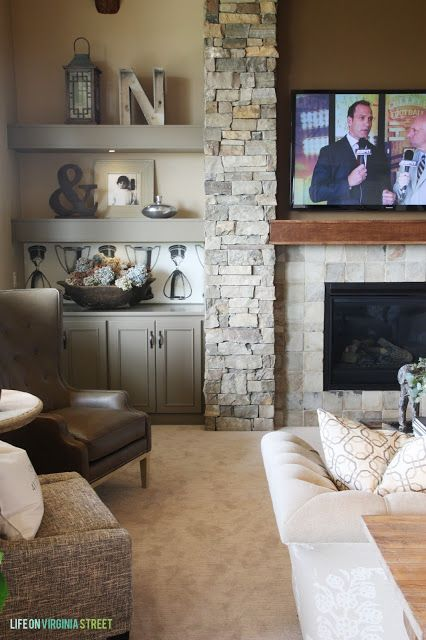 Living Room with stone fireplace wall, wood mantel and gray built-in shelves and cabinets.