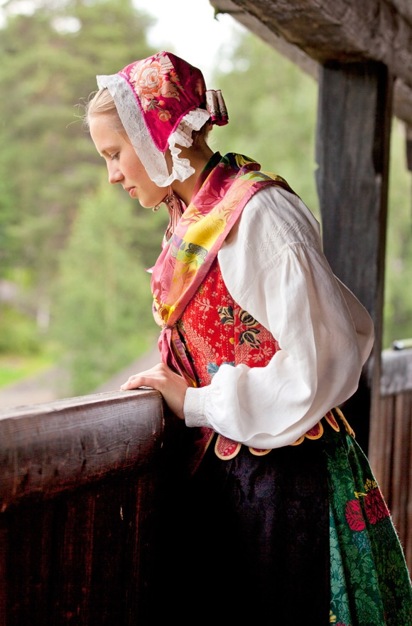 The Hedemark bunad influenced by fashion of the Rococco period. The bonnet in brocaded silk, botthuve, is fastened with silk ribbons under the chin and has a silk bow in the neck. The white cotton under-lace is known as skru. Copyright-Laila-Duran