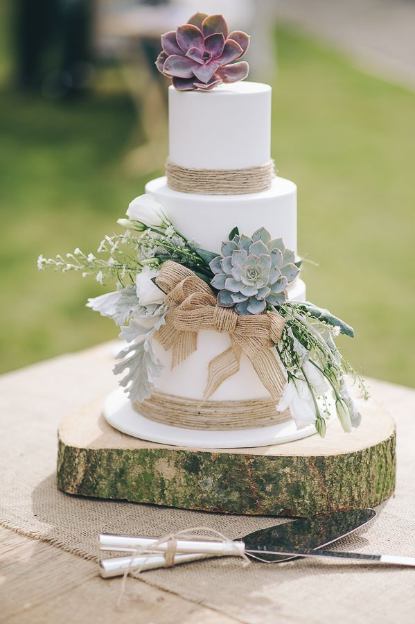 Succulent covered, nature inspired, rustic wedding cake on a wooden base with hessian runner.   A three tier modern wedding cake.   Taken from: A Nature-Inspired, Rustic Wedding in Cornwall: Styled Shoot Inspiration  For more inspiration visit www.weddingsite.co.uk