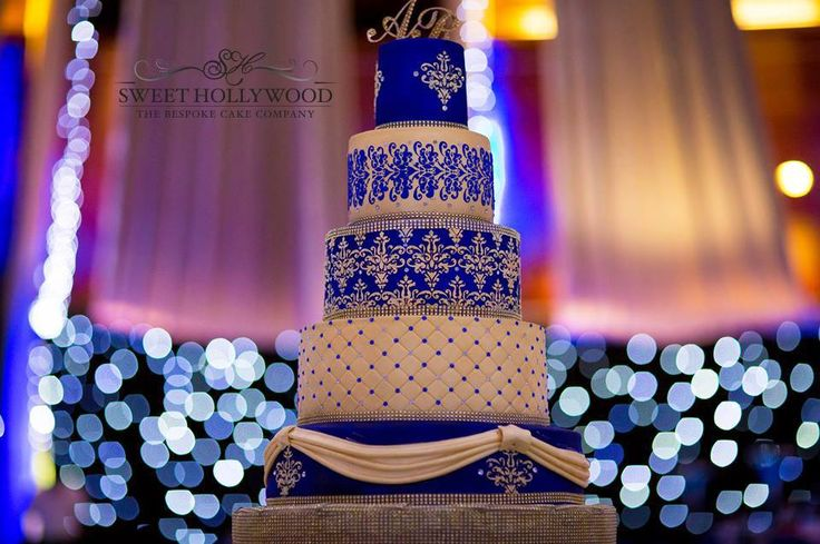 """Presenting our champagne gold and royal blue Show Stopper wedding cake! Our superior size of 5 1/2 inches high each with the bottom tier being 18"""" wide created an impact in the venue.  www.sweethollywood.com"""