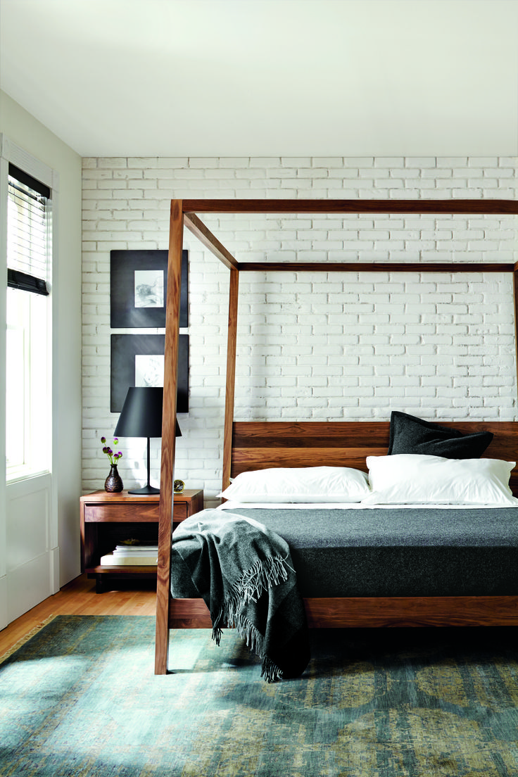 White-washed brick complements a minimal wooden bed frame in this sleek, simple space.