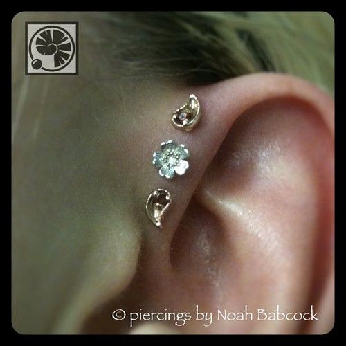 Triple forward helix piercing with whitegold, rosegold and garnet jewelry by BVLA at Evolution Piercing.