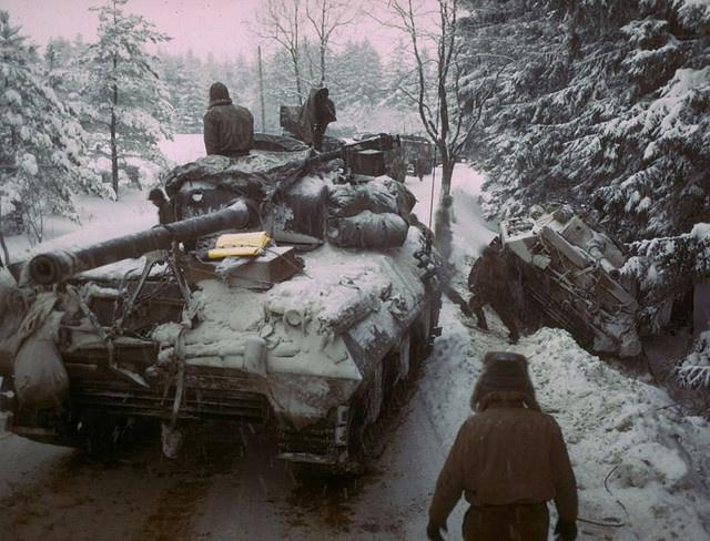 El tanque de americano Sherman M4 se mueve por delante de otro carro de arma que se deslizó del camino helado en el Bosque Ardennes durante el empuje para parar tropas de alemán que avanzan. el 20 de diciembre de 1944