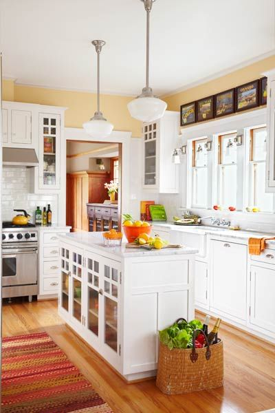 This period-style soft yellow kitchen features schoolhouse style pendant lights…