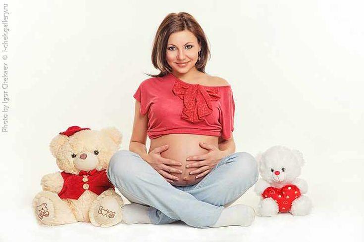 беременная мама сидит вместе с плюшевыми медвежатами
