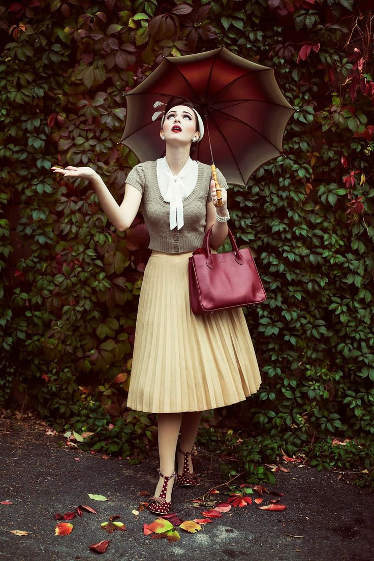 The greens and reds have echoes of the poison apples in Snow White. The luscious colours of the background perfectly contrast against the pure and innocent colours of the outfit. Subtle taupe and delicate buttermilk are set off against the perfectly places accessories. A blood red handbag, shoes and umbrella. A style masterpiece made all the better by some wonderful photography.