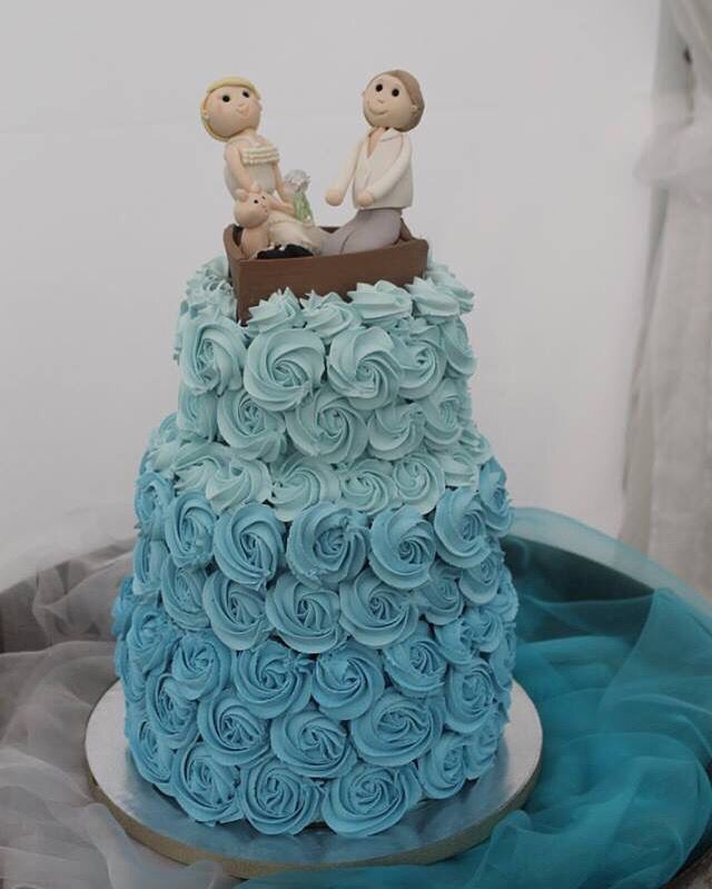 Ombré blue Rosettes for this 3 tiered wedding cake, with the bride, groom and the cat and dog in a boat for the topper