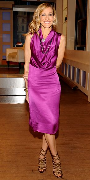 Sarah Jessica Parker wearing a fuchsia silk dress with strappy sandals, a Stephen Russell heart-shaped diamond necklace and a string of pearls.