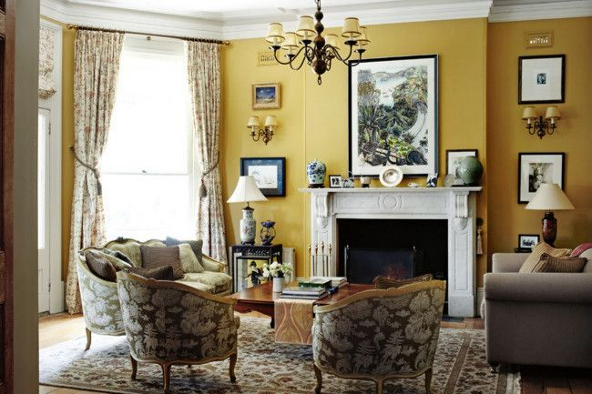 A sitting room with golden yellow walls and a mix of antique and modern collectibles.